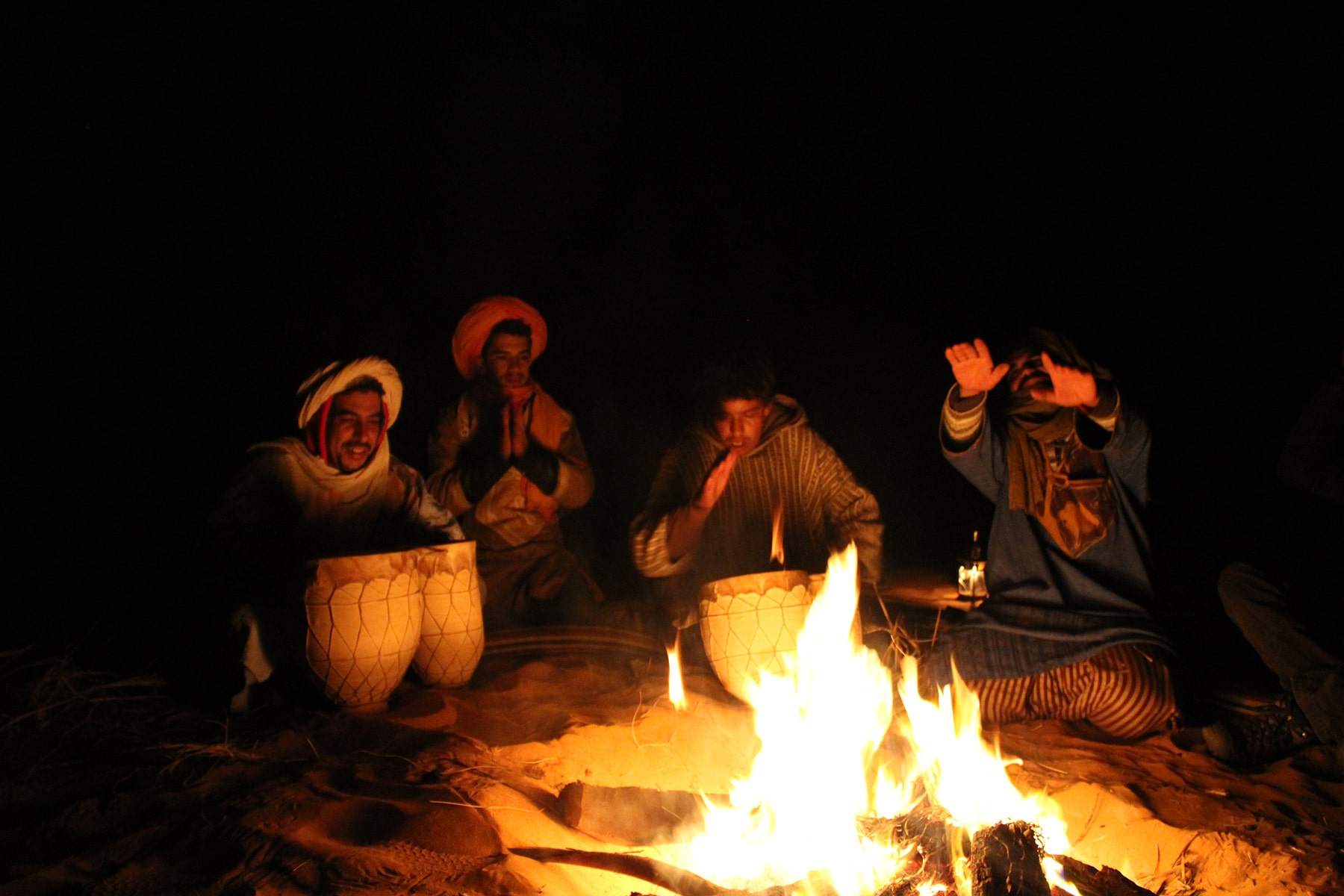 Berber singing and playing music around bonfire in Sahara desert