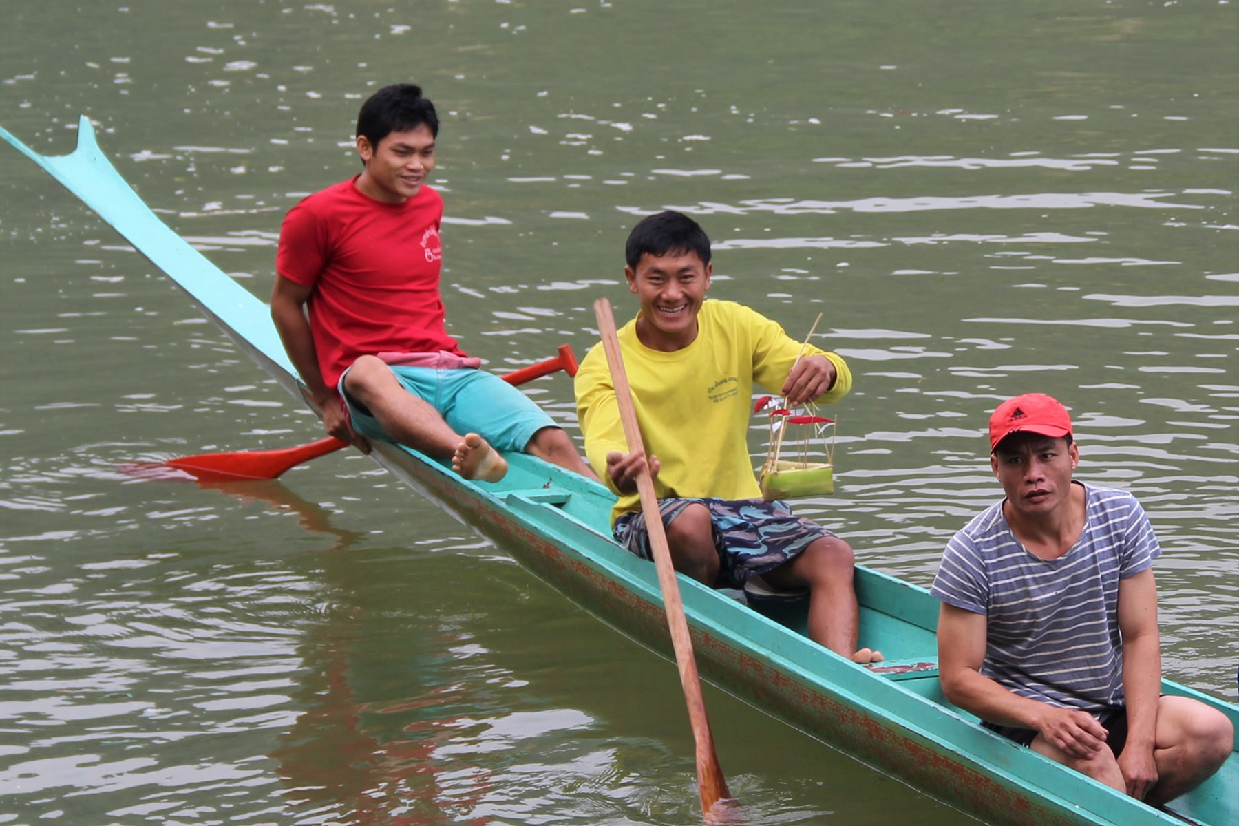 Laotians Village people on the boat holding tiny bamboo boats as good luck charm