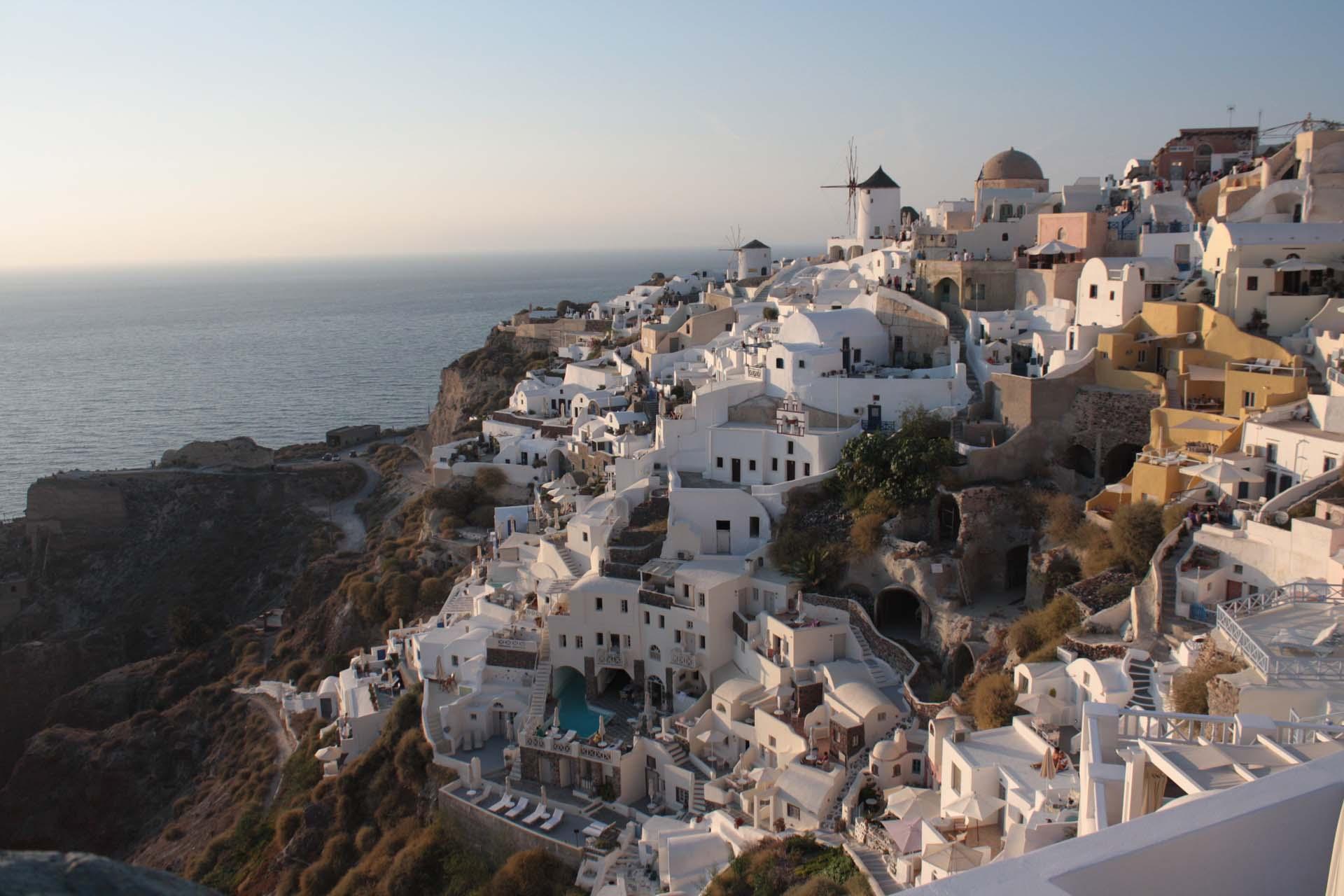 Il tramonto riflesso sulla città di Oia a Santorini case bianche mulini