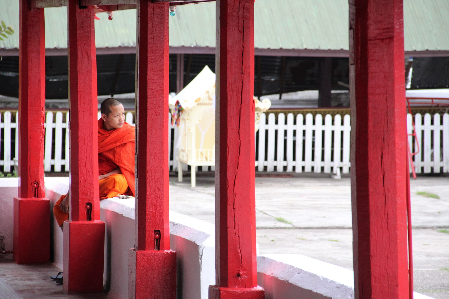 A monk between red columns in Wat Mai Suwannaphumaham Luang Prabang, Laos