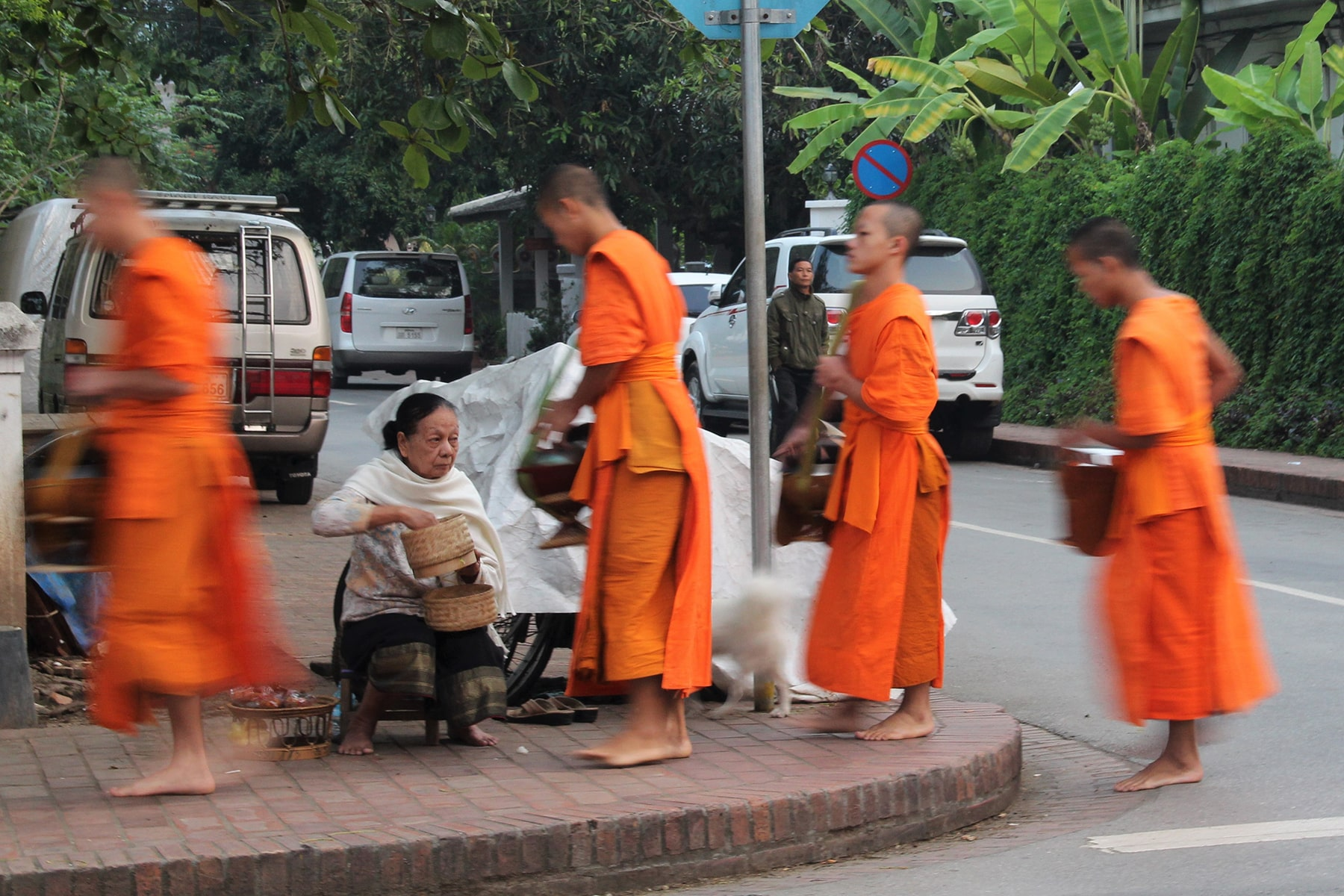 A woman offering some rice to monks during the morning alms ritual in Luang Prabang, Laos