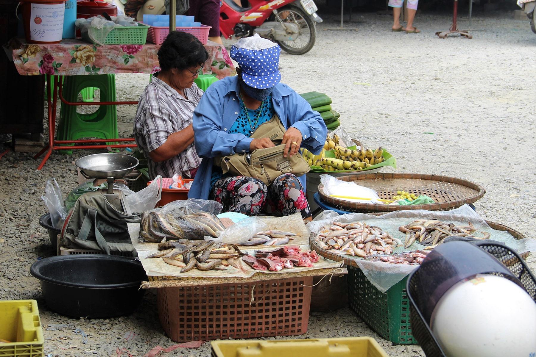 Femme vendant du poisson au marché de jour de Sukhothaï assise par terre