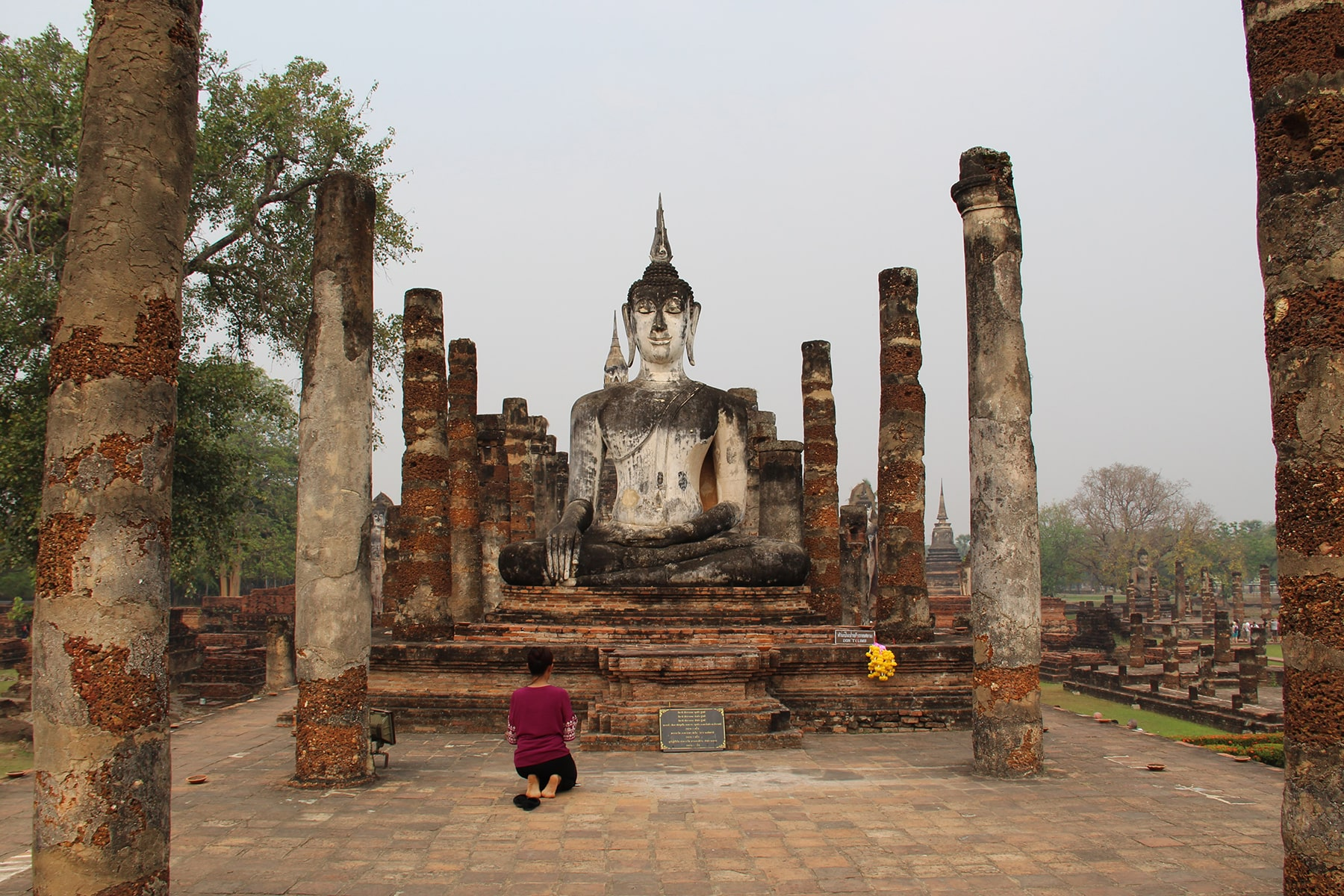Femme priant devant la statue blanche de Bouddha entre ruines de colonnes dans le hall d'ordination au Wat Mahathat - Parc historique de Sukhothaï