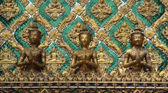 Persone che pregano come decori verdi e dorati del Palazzo reale di Bangkok