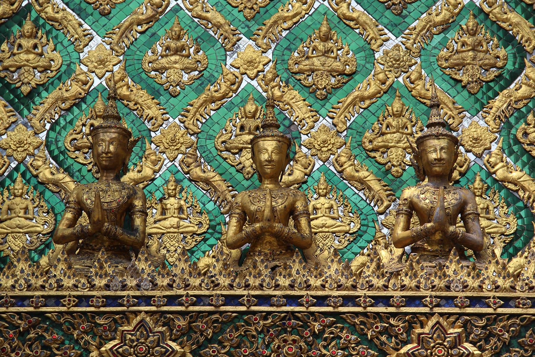 Praying figures as green gold decorations in Bangkok Grand Palace
