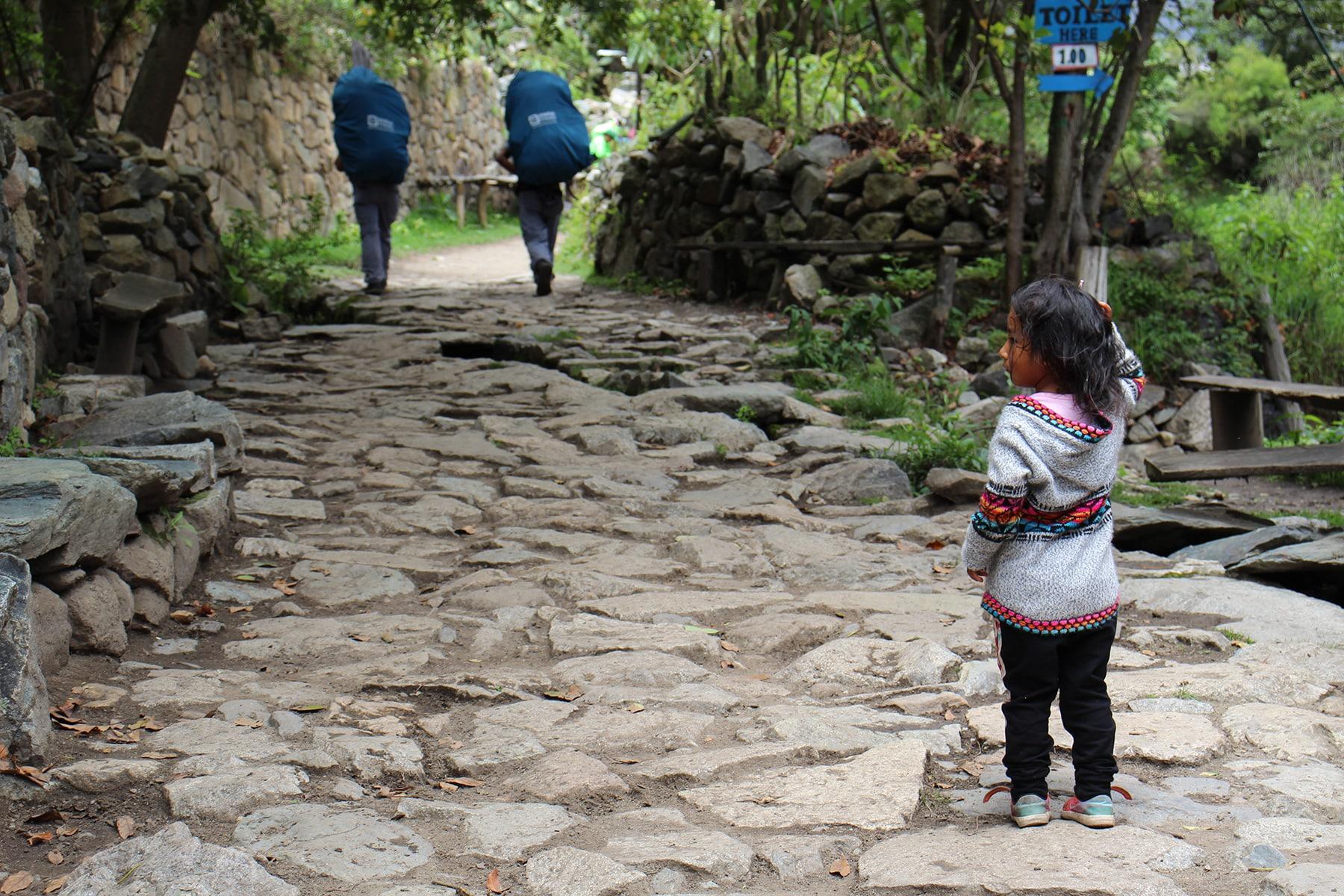 Una bambina sul inca trail guarda i passanti