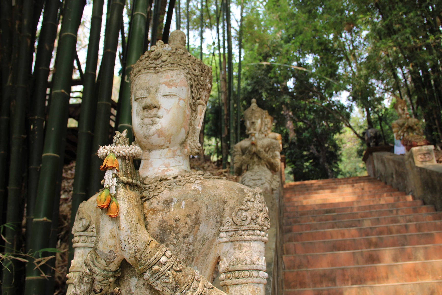 Praying statue with offerings in Chiang Mai Wat Pha Lat temple