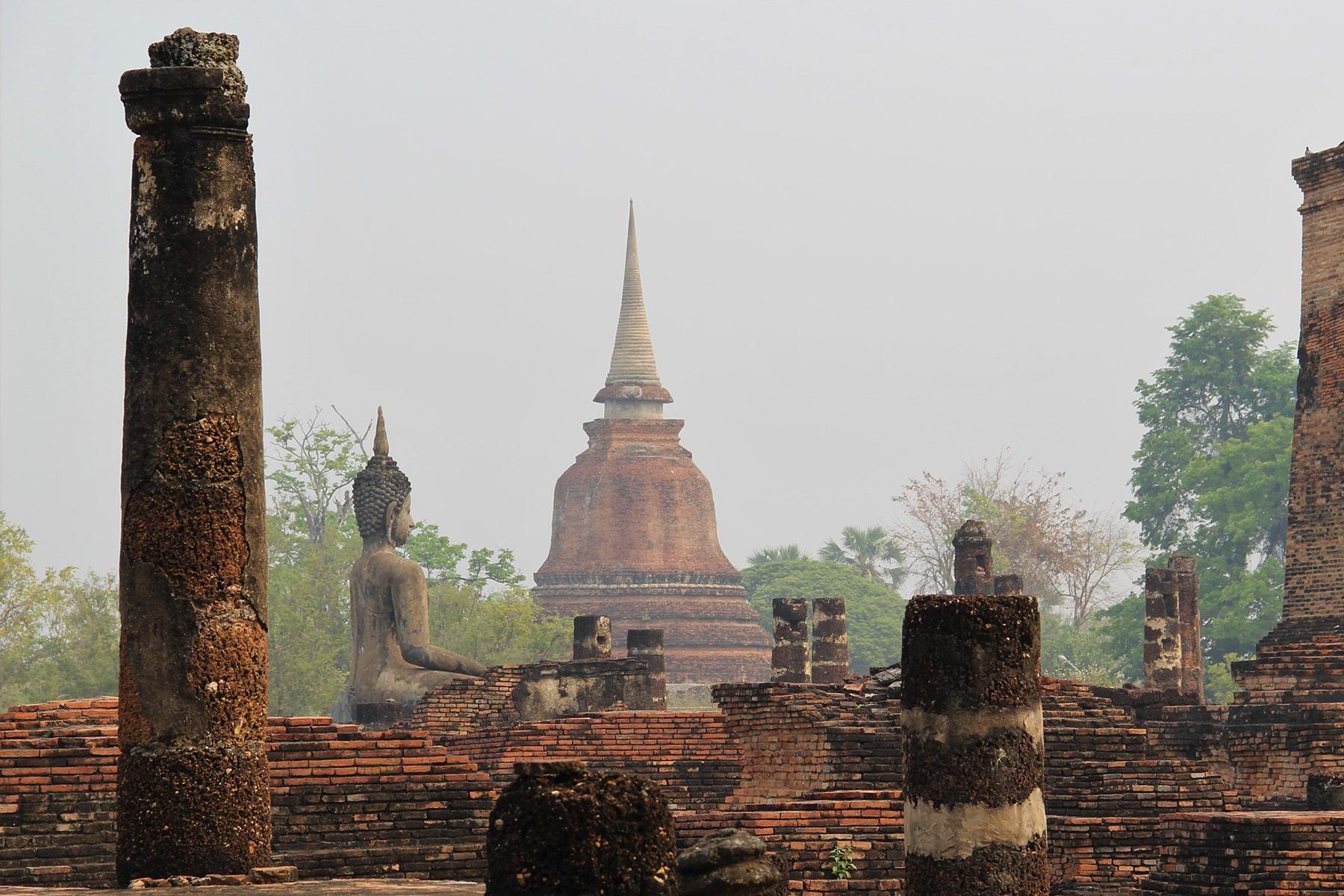 Colonnes, Statue de Bouddha et Stupa dans le brouillard dans le parc historique de Sukhothaï