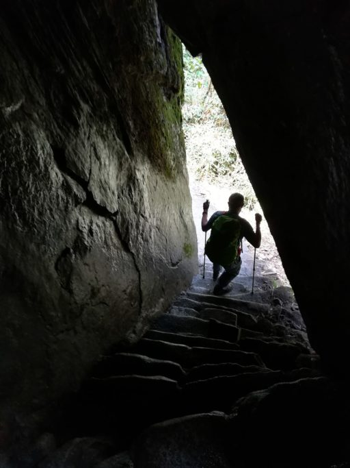 Man descending steps in cave inca trail