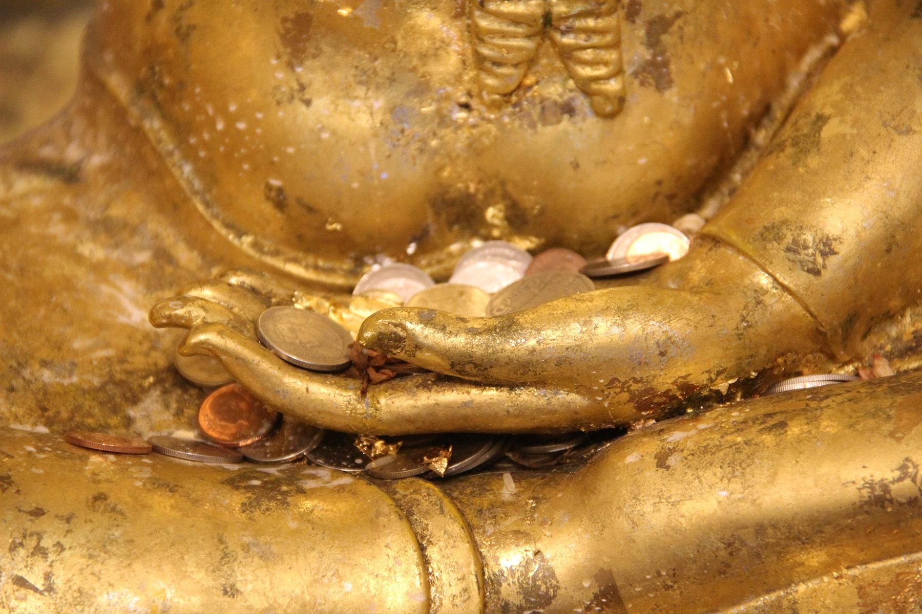Mano dorata di Buddha con offerte nel tempio della montagna d'oro a Bangkok
