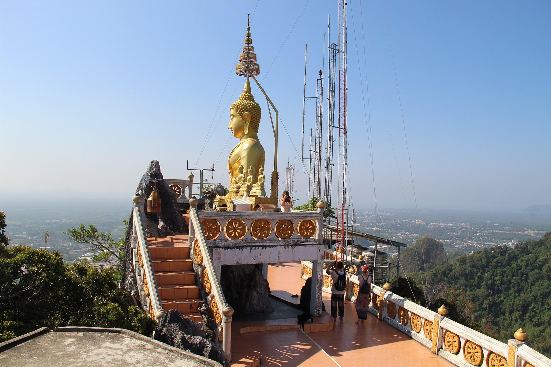 Statue de Buddha en haut du Wat Tham Suea à Krabi avec vue sur les collines vertes