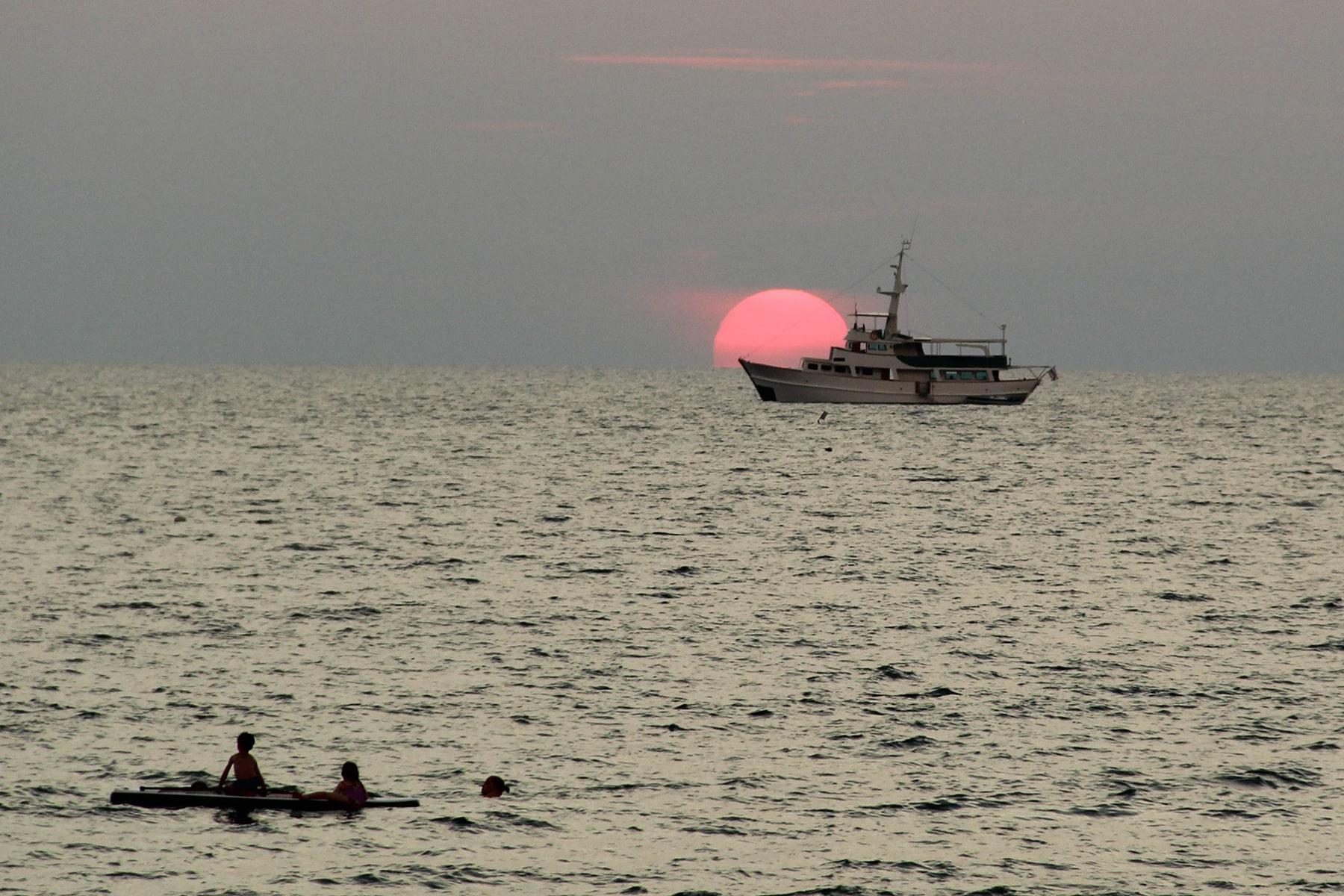 Coucher de soleil Koh Lanta ; soleil rouge qui se couche derrière un bateau