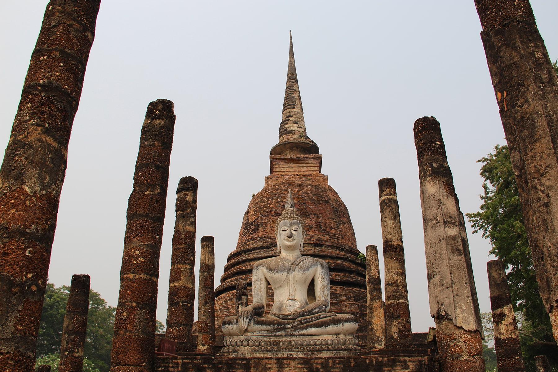 Bouddha et stupa entourés par des colonnes au parc historique de Sukhothaï