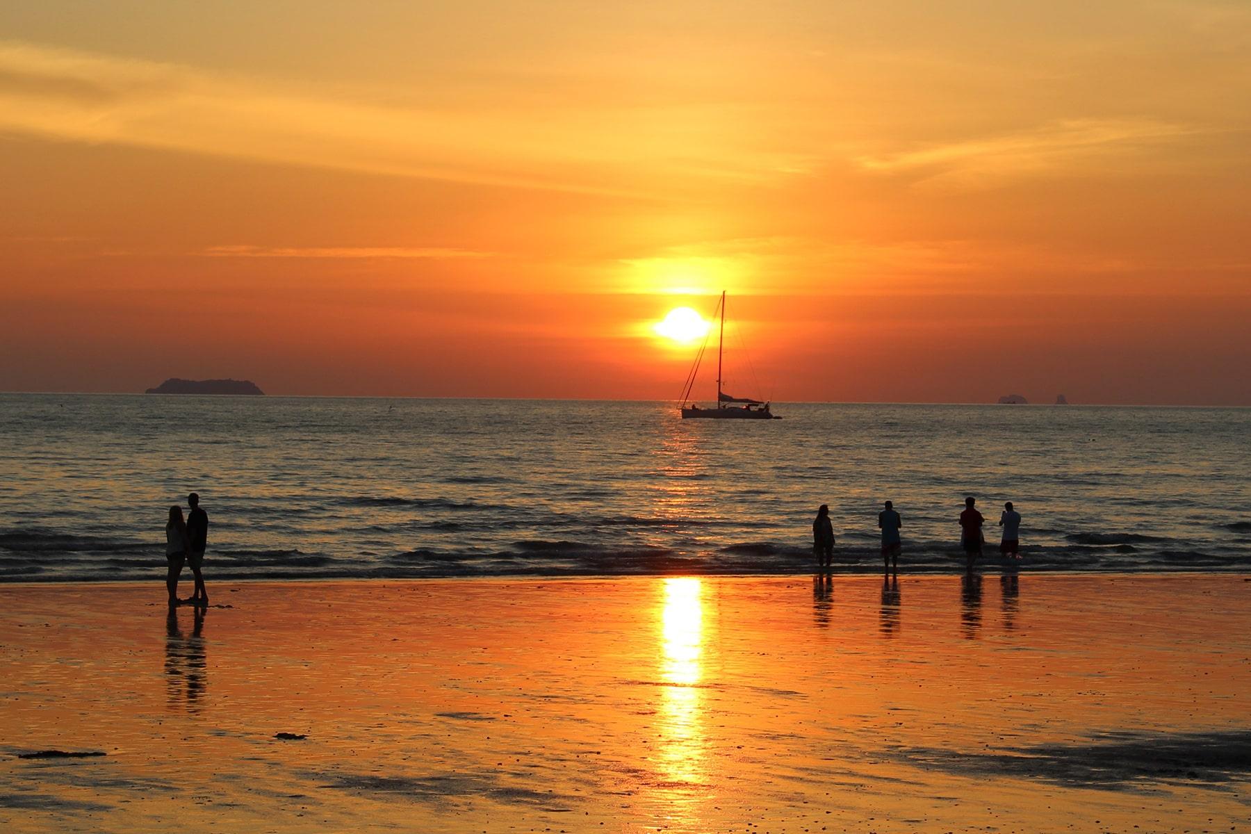 Coucher de soleil orange qui se réflète sur une plage à Koh Lanta