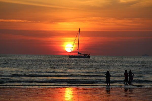 Coucher de soleil derrière un bateau à Koh Lanta ressemblant à une boule de feu