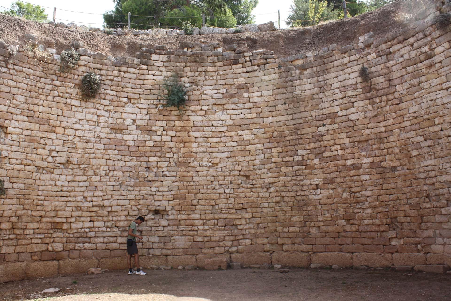 Uomo dentro una tomba a tholos a Micene, un grande buco tondo