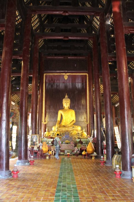 Interior of wooden Wat Phan Tao temple with golden Buddha in Chiang Mai