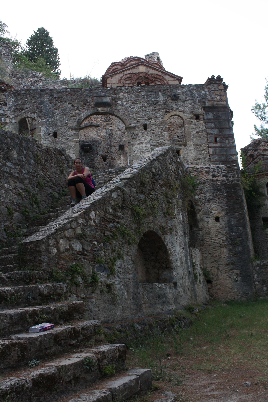 Donne seduta sulle scale di un monastero in rovina a Mistra